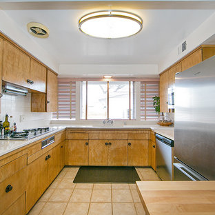 Inspiration for a mid-sized midcentury u-shaped eat-in kitchen in Orange County with flat-panel cabinets, light wood cabinets, laminate benchtops, stainless steel appliances, ceramic floors and with island.