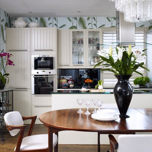 This is an example of a mid-sized transitional u-shaped eat-in kitchen in London with louvered cabinets, white cabinets, glass benchtops, black splashback, glass sheet splashback, stainless steel appliances, a peninsula, dark hardwood floors and brown floor.