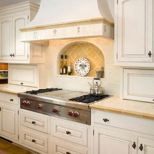 サンタバーバラの地中海スタイルのおしゃれなキッチン (アンダーカウンターシンク、レイズドパネル扉のキャビネット、白いキャビネット、タイルカウンター、白いキッチンパネル、白い調理設備、セラミックタイルのキッチンパネル、淡色無垢フローリング) の写真