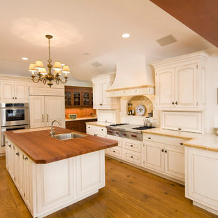 Design ideas for a large mediterranean l-shaped eat-in kitchen in Santa Barbara with an undermount sink, raised-panel cabinets, white cabinets, tile benchtops, panelled appliances, ceramic splashback, light hardwood floors, with island and beige splashback.