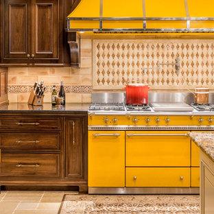 Réalisation d'une grande cuisine américaine tradition avec un évier de ferme, un placard avec porte à panneau encastré, un plan de travail en quartz, une crédence beige, une crédence en carreau de porcelaine, un électroménager de couleur, 2 îlots, des portes de placard en bois sombre et un sol beige.