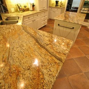 ダラスの広いトラディショナルスタイルのおしゃれなキッチン (アンダーカウンターシンク、レイズドパネル扉のキャビネット、白いキャビネット、御影石カウンター、黒い調理設備、茶色いキッチンパネル、石タイルのキッチンパネル、テラコッタタイルの床、赤い床) の写真