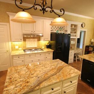 ダラスの大きいトラディショナルスタイルのおしゃれなキッチン (アンダーカウンターシンク、レイズドパネル扉のキャビネット、白いキャビネット、御影石カウンター、黒い調理設備、茶色いキッチンパネル、石タイルのキッチンパネル、テラコッタタイルの床、赤い床) の写真