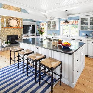 ボストンのビーチスタイルのおしゃれなアイランドキッチン (エプロンフロントシンク、ガラス扉のキャビネット、白いキャビネット、シルバーの調理設備の、グレーのキッチンカウンター、淡色無垢フローリング) の写真
