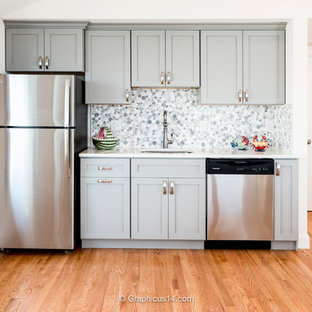 Design ideas for a small beach style single-wall open plan kitchen in New York with an undermount sink, recessed-panel cabinets, grey cabinets, limestone benchtops, multi-coloured splashback, ceramic splashback, stainless steel appliances, medium hardwood floors and no island.