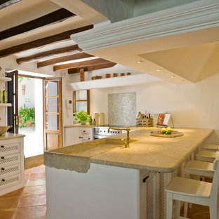 Inspiration for a mediterranean kitchen in London with an integrated sink, white cabinets and terracotta flooring.