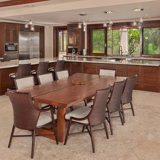 Offene, Große Tropenstil Küche in L-Form mit Schrankfronten im Shaker-Stil, dunklen Holzschränken, Marmor-Arbeitsplatte, Kalkstein, Kücheninsel, beigem Boden, Unterbauwaschbecken und Küchengeräten aus Edelstahl in Hawaii