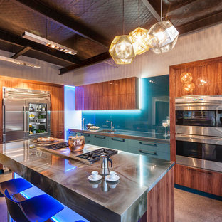 This is an example of a mid-sized modern l-shaped open plan kitchen in Los Angeles with an integrated sink, flat-panel cabinets, beige cabinets, onyx benchtops, blue splashback, glass sheet splashback, stainless steel appliances, concrete floors, with island and beige floor.