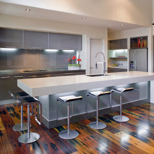 Mid-sized modern open concept kitchen designs - Example of a mid-sized minimalist single-wall medium tone wood floor and brown floor open concept kitchen design in Los Angeles with an undermount sink, glass-front cabinets, gray cabinets, quartz countertops, gray backsplash, glass sheet backsplash, paneled appliances and an island