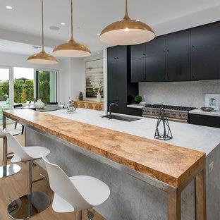 オレンジカウンティの広いミッドセンチュリースタイルのおしゃれなキッチン (ドロップインシンク、フラットパネル扉のキャビネット、黒いキャビネット、大理石カウンター、グレーのキッチンパネル、大理石のキッチンパネル、シルバーの調理設備、無垢フローリング、茶色い床、グレーのキッチンカウンター) の写真