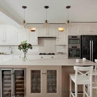Transitional porcelain floor kitchen photo in Dublin with an undermount sink, beige cabinets, quartzite countertops, beige backsplash, stone slab backsplash, an island, recessed-panel cabinets and black appliances