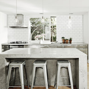This is an example of a medium sized urban single-wall kitchen with flat-panel cabinets, stainless steel cabinets, concrete worktops, white splashback, metro tiled splashback, stainless steel appliances, light hardwood flooring, an island, beige floors and an integrated sink.
