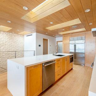 Idéer för att renovera ett mycket stort funkis vit vitt kök, med en enkel diskho, skåp i shakerstil, skåp i ljust trä, bänkskiva i kvarts, beige stänkskydd, stänkskydd i glaskakel, rostfria vitvaror, ljust trägolv, en köksö och gult golv