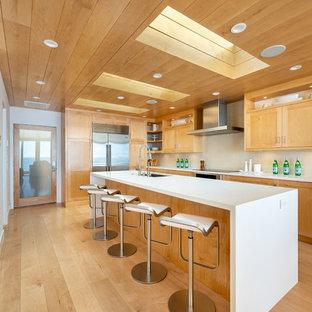 ロサンゼルスの巨大なコンテンポラリースタイルのおしゃれなキッチン (シングルシンク、シェーカースタイル扉のキャビネット、クオーツストーンカウンター、ベージュキッチンパネル、ガラスタイルのキッチンパネル、シルバーの調理設備の、白いキッチンカウンター、中間色木目調キャビネット、無垢フローリング、茶色い床) の写真