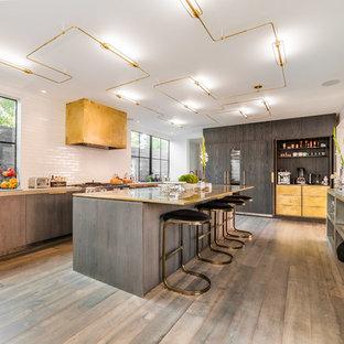 ロサンゼルスの巨大なコンテンポラリースタイルのおしゃれなキッチン (白いキッチンパネル、フラットパネル扉のキャビネット、サブウェイタイルのキッチンパネル、パネルと同色の調理設備、コンクリートカウンター、グレーのキャビネット、グレーの床、無垢フローリング) の写真