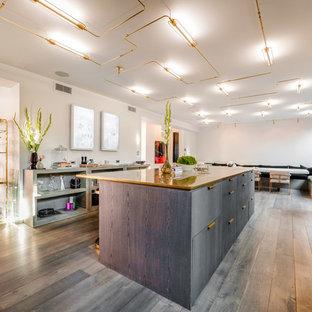 Geräumige Moderne Küche mit Küchenrückwand in Weiß, Kücheninsel, flächenbündigen Schrankfronten, grauen Schränken, Kupfer-Arbeitsplatte, grauem Boden und braunem Holzboden in Los Angeles