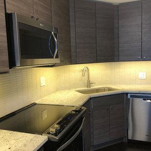 Mittelgroße Moderne Wohnküche in U-Form mit Waschbecken, flächenbündigen Schrankfronten, dunklen Holzschränken, Granit-Arbeitsplatte, Küchenrückwand in Beige, Rückwand aus Mosaikfliesen, Küchengeräten aus Edelstahl, dunklem Holzboden, Kücheninsel und schwarzem Boden in Chicago