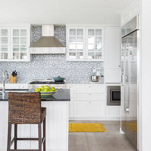 This is an example of a mid-sized beach style l-shaped kitchen in Los Angeles with an undermount sink, louvered cabinets, white cabinets, grey splashback, stainless steel appliances, light hardwood floors, with island, beige floor and black benchtop.