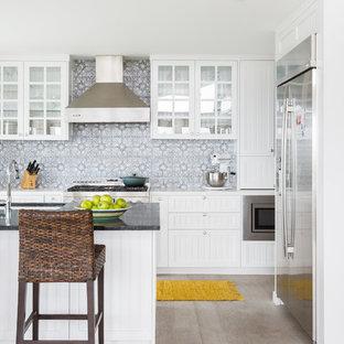 ロサンゼルスの中くらいのビーチスタイルのおしゃれなキッチン (アンダーカウンターシンク、ルーバー扉のキャビネット、白いキャビネット、グレーのキッチンパネル、シルバーの調理設備、淡色無垢フローリング、ベージュの床、珪岩カウンター、セメントタイルのキッチンパネル、白いキッチンカウンター) の写真