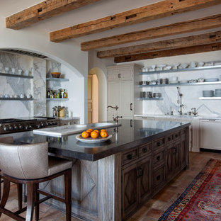 Mediterranean enclosed kitchen designs - Tuscan terra-cotta floor enclosed kitchen photo in Los Angeles with recessed-panel cabinets, beige cabinets, white backsplash, an island and marble backsplash