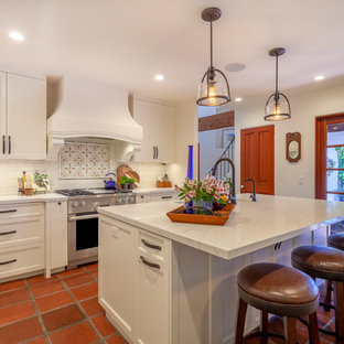 ロサンゼルスの中くらいの地中海スタイルのおしゃれなキッチン (白いキャビネット、シルバーの調理設備、白いキッチンカウンター、シェーカースタイル扉のキャビネット、マルチカラーのキッチンパネル、テラコッタタイルの床、オレンジの床) の写真