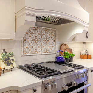 Photo of a mid-sized mediterranean eat-in kitchen in Los Angeles with an undermount sink, recessed-panel cabinets, white cabinets, quartz benchtops, white splashback, porcelain splashback, stainless steel appliances, cement tiles, with island, red floor and white benchtop.
