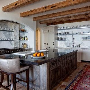 ロサンゼルスの地中海スタイルのおしゃれなキッチン (ドロップインシンク、落し込みパネル扉のキャビネット、ベージュのキャビネット、大理石のキッチンパネル、シルバーの調理設備、テラコッタタイルの床、赤い床) の写真