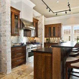 Modelo de cocina en L, tradicional renovada, con armarios con paneles empotrados, puertas de armario de madera en tonos medios, salpicadero metalizado, salpicadero de metal y electrodomésticos de acero inoxidable