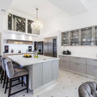 Foto de cocina en L, tradicional, grande, abierta, con armarios con paneles empotrados, puertas de armario grises, salpicadero blanco, electrodomésticos de acero inoxidable, una isla y encimeras blancas