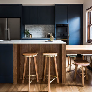 This is an example of a transitional galley kitchen in Melbourne with an undermount sink, shaker cabinets, blue cabinets, grey splashback, marble splashback, black appliances, medium hardwood floors, with island, brown floor and grey benchtop.