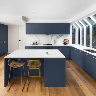 Design ideas for a large contemporary u-shaped open plan kitchen in Melbourne with blue cabinets, marble benchtops, white splashback, marble splashback, with island, a drop-in sink, flat-panel cabinets, stainless steel appliances, medium hardwood floors, brown floor and white benchtop.