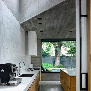 Exempel på ett stort modernt vit vitt kök, med släta luckor, skåp i ljust trä, bänkskiva i kvarts, vitt stänkskydd, stänkskydd i keramik, rostfria vitvaror, en köksö, grått golv, en undermonterad diskho och terrazzogolv