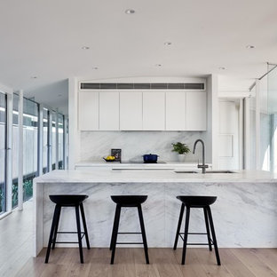 Contemporary galley kitchen in Melbourne with an undermount sink, flat-panel cabinets, white cabinets, medium hardwood floors, with island, brown floor and white benchtop.