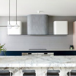 Design ideas for a contemporary kitchen in Melbourne with flat-panel cabinets, grey splashback, stainless steel appliances, with island and white benchtop.
