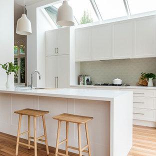メルボルンの中くらいのコンテンポラリースタイルのおしゃれなキッチン (シェーカースタイル扉のキャビネット、白いキャビネット、珪岩カウンター、セラミックタイルのキッチンパネル、淡色無垢フローリング、白いキッチンカウンター、アンダーカウンターシンク、パネルと同色の調理設備、ベージュの床、三角天井) の写真