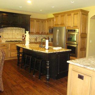 グランドラピッズの大きいトランジショナルスタイルのおしゃれなキッチン (レイズドパネル扉のキャビネット、中間色木目調キャビネット、大理石カウンター、ベージュキッチンパネル、無垢フローリング) の写真