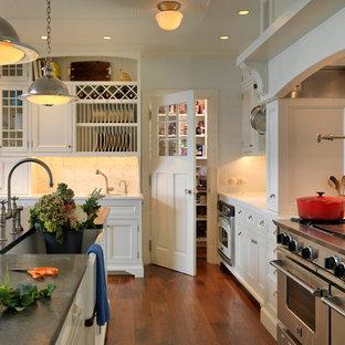 Inspiration för ett vintage kök, med en rustik diskho, luckor med infälld panel, vita skåp, beige stänkskydd, rostfria vitvaror, en köksö och mörkt trägolv