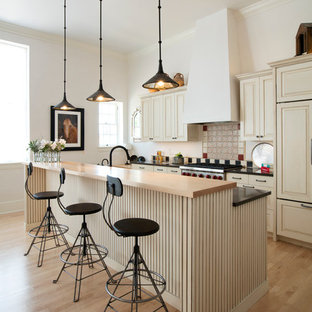 Inspiration for a mid-sized traditional l-shaped open plan kitchen in Albuquerque with raised-panel cabinets, beige cabinets, beige splashback, panelled appliances, light hardwood floors, with island, an undermount sink, granite benchtops, ceramic splashback and black benchtop.