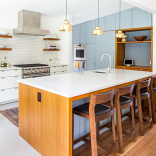 Design ideas for a midcentury l-shaped eat-in kitchen in Los Angeles with an undermount sink, flat-panel cabinets, blue cabinets, quartz benchtops, white splashback, ceramic splashback, stainless steel appliances, porcelain floors, with island, grey floor and white benchtop.