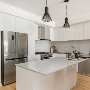 Inspiration for a mid-sized contemporary l-shaped kitchen in Perth with white cabinets, quartz benchtops, grey splashback, stainless steel appliances, laminate floors, with island, grey benchtop, flat-panel cabinets, a drop-in sink and beige floor.