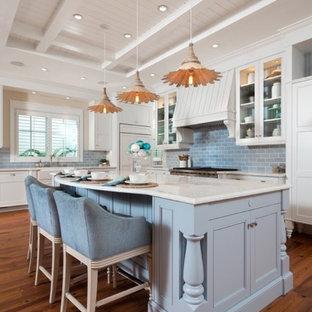 マイアミのビーチスタイルのおしゃれなアイランドキッチン (エプロンフロントシンク、白いキャビネット、青いキッチンパネル、サブウェイタイルのキッチンパネル、無垢フローリング、白いキッチンカウンター、パネルと同色の調理設備、シェーカースタイル扉のキャビネット) の写真