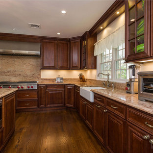 Expansive u-shaped kitchen/diner in New York with a belfast sink, raised-panel cabinets, brown cabinets, beige splashback, stainless steel appliances, plywood flooring and an island.