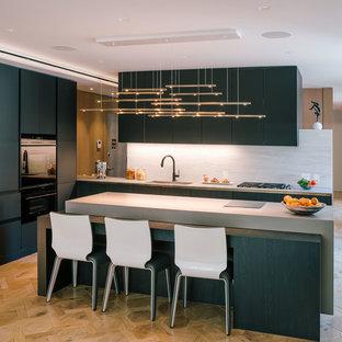 Idee per una grande cucina minimalista con lavello sottopiano, ante lisce, ante nere, top in cemento, paraspruzzi grigio, paraspruzzi in lastra di pietra, elettrodomestici neri, parquet chiaro, isola e pavimento beige