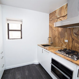 Small modern enclosed kitchen pictures - Enclosed kitchen - small modern galley dark wood floor and black floor enclosed kitchen idea in New York with an undermount sink, flat-panel cabinets, white cabinets, granite countertops, brown backsplash, stone slab backsplash, stainless steel appliances and no island