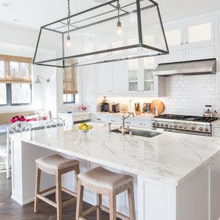 ロサンゼルスのビーチスタイルのおしゃれなキッチン (中間色木目調キャビネット、白いキッチンパネル、磁器タイルのキッチンパネル、シルバーの調理設備、無垢フローリング、茶色い床) の写真