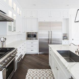 ロサンゼルスのビーチスタイルのおしゃれなキッチン (中間色木目調キャビネット、白いキッチンパネル、磁器タイルのキッチンパネル、シルバーの調理設備の、無垢フローリング、茶色い床) の写真