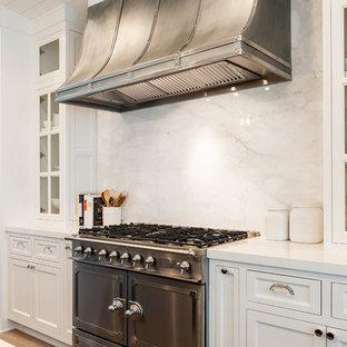 ロサンゼルスの大きいカントリー風おしゃれなキッチン (アンダーカウンターシンク、落し込みパネル扉のキャビネット、白いキャビネット、人工大理石カウンター、白いキッチンパネル、大理石の床、パネルと同色の調理設備、淡色無垢フローリング、白いキッチンカウンター) の写真