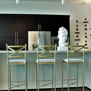 Esempio di una piccola cucina minimal con lavello sottopiano, ante lisce, ante in legno bruno, top in granito, elettrodomestici in acciaio inossidabile, parquet scuro, isola e pavimento nero