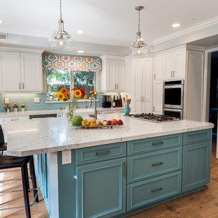 ロサンゼルスの広いビーチスタイルのおしゃれなキッチン (エプロンフロントシンク、インセット扉のキャビネット、白いキャビネット、クオーツストーンカウンター、青いキッチンパネル、ガラスタイルのキッチンパネル、シルバーの調理設備、淡色無垢フローリング、マルチカラーの床) の写真