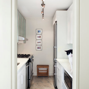 Small contemporary galley separate kitchen in New York with a drop-in sink, flat-panel cabinets, white cabinets, limestone benchtops, stainless steel appliances, ceramic floors and no island.
